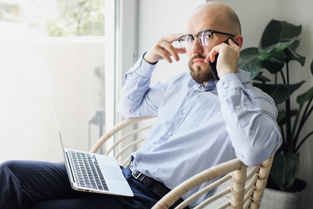 Zamknij się młody biznesmen w okularach z laptopem, siedząc na krześle