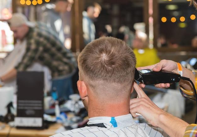 Zamknij się młody człowiek mający strzyżenie i bok głowy ogolony przez stylistę w zakładzie fryzjerskim