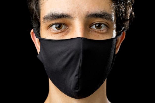Zamknij się młody człowiek ubrany w czarną maskę. koncepcja okresu kwarantanny koronawirusa covid-19 pandemii.