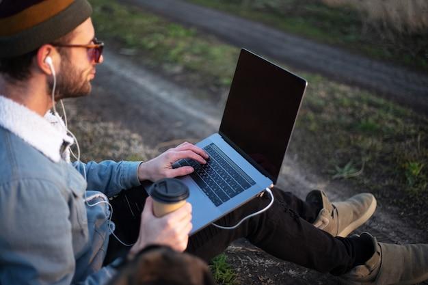Zamknij się młody mężczyzna siedzi z laptopem na nogach i filiżankę kawy w ręku