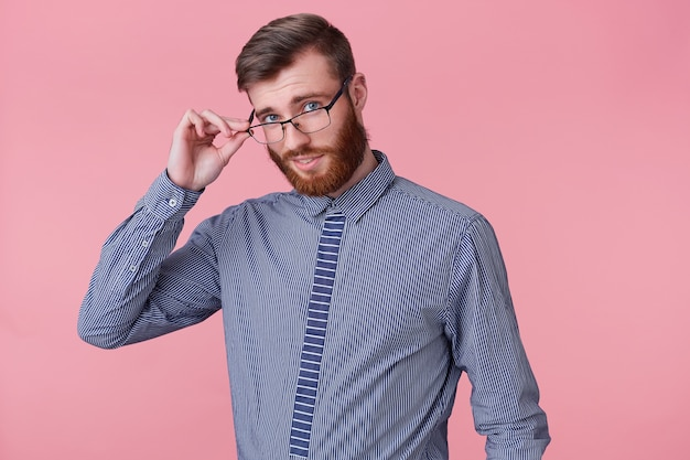 Zamknij się młody przystojny brodaty mężczyzna pozowanie na kamery na białym tle na różowym tle i uśmiechnięty, trzymając ręką okulary i patrząc przez nie.