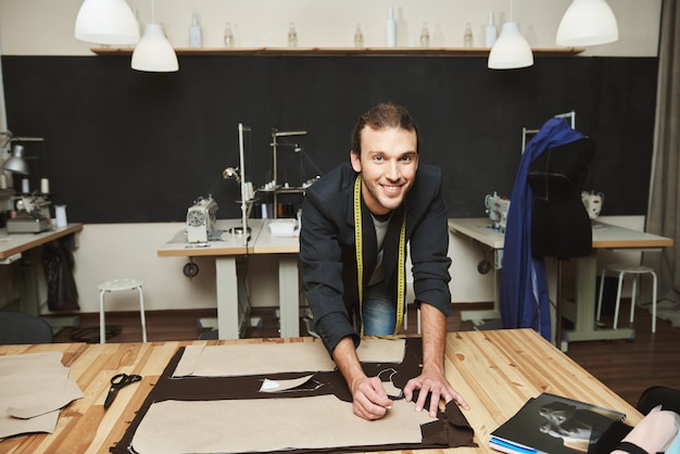 Zamknij się młody wesoły atrakcyjny męski projektant ubrań ze stylową fryzurą w garniturze pracuje nad nową kolekcją w swoim warsztacie, wycinając części ubrania.