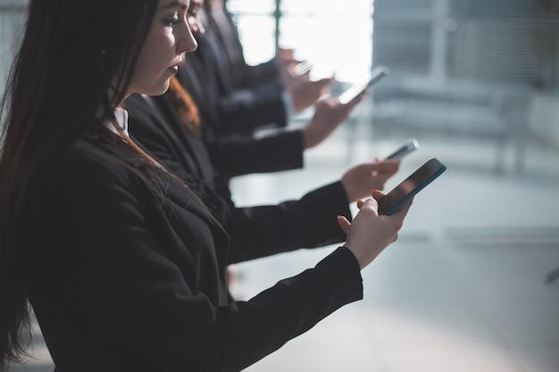 Zamknij się. młodzi ludzie biznesu ze smartfonami w kolejce. ludzie i technologia