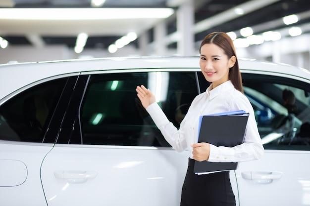 Zamknij się na azjatyckiej sprzedawczyni w auto sprzedaży samochodów