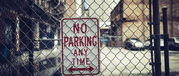 Zamknij się na brak parkingu w dowolnym momencie znak na ogrodzeniu