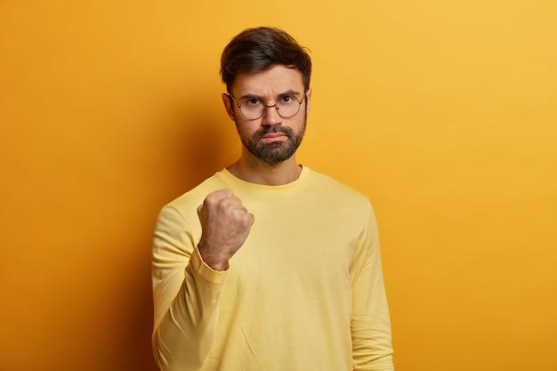 Zamknij się na brodaty młody mężczyzna w okularach na białym tle