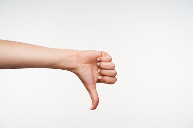 Zamknij się na dłoni młodych atrakcyjnych kobiet pokazując w dół z kciukiem