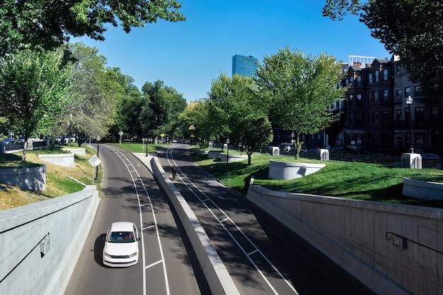 Zamknij się na miejskiej drodze z samochodem i zielenią