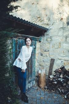 Zamknij się na młodej kobiecie w pobliżu wiejskiej szopy