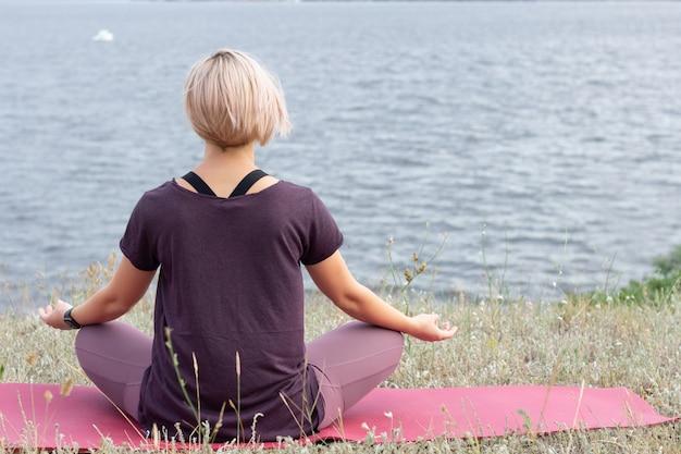 Zamknij się na młodej kobiety medytacji w polu przed rzeką