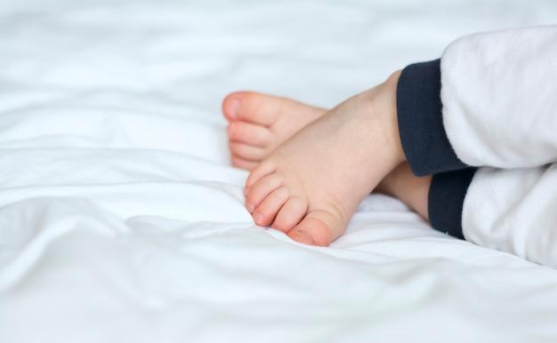 Zamknij się na nogach śpiącego dziecka w łóżku