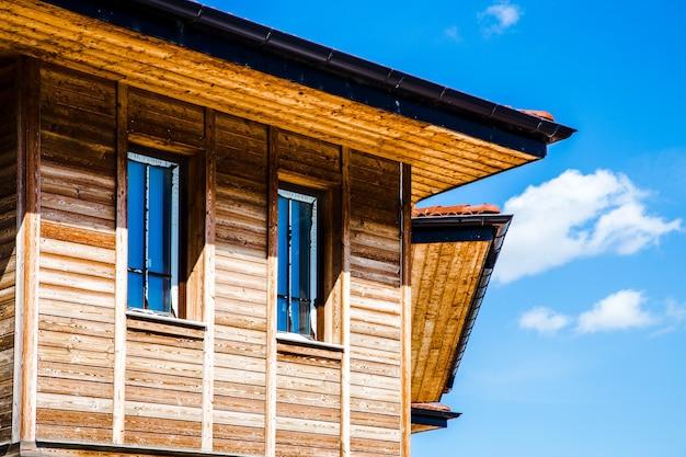 Zamknij się na oknach drewnianego domu nad błękitne niebo