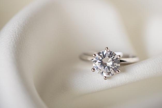 Zamknij się na pierścionek z brylantem na białej tkaninie
