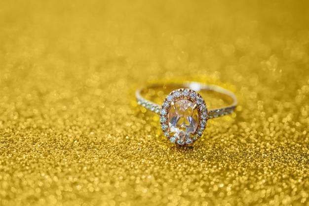 Zamknij się na pierścionek z brylantem na złotym brokacie