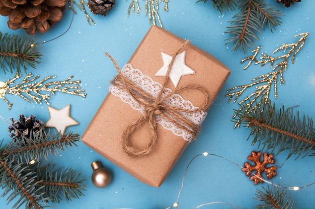 Zamknij się na prezent świąteczny z gałązkami jodły i złotymi