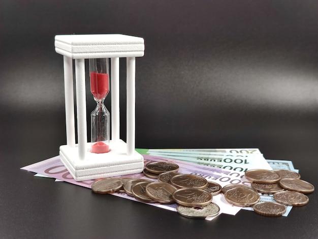 Zamknij się na rachunkach i monetach obok klepsydry