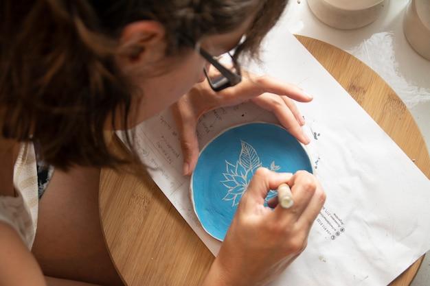 Zamknij się na rękach pracujących nad glinianą dekoracją płyty