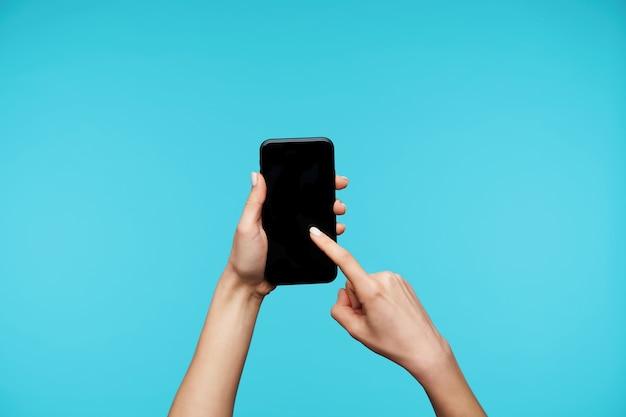Zamknij się na rękach z białym manicure, trzymając smartfon i przesuwając po ekranie