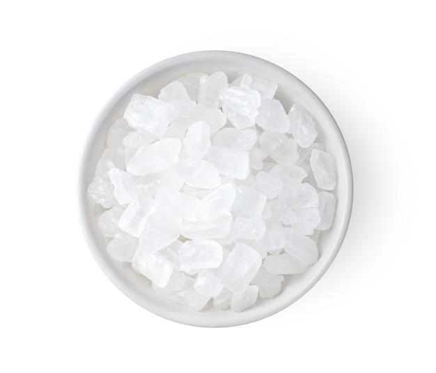 Zamknij się na rock cukru w białej misce na białym tle