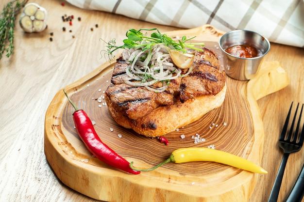 Zamknij się na smakowitej szyjce z grilla podanej na chlebie pita z cebulą, mikrozielonymi i ostrą papryką. drewniany mur. skopiuj miejsce selektywne ustawianie ostrości