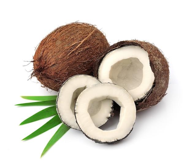Zamknij się na świeżych kokosach z liśćmi na białym tle
