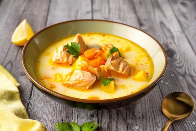 Zamknij się na talerzu z pyszną jasną zupą rybną z łososia
