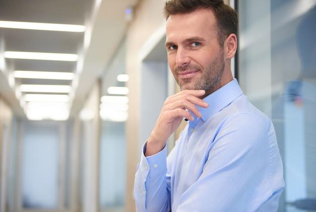Zamknij się na zamyślonego mężczyznę na korytarzu biura