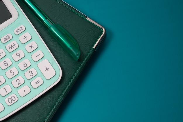 Zamknij się niebieski kalkulator i notatnik na kolorowym tle.