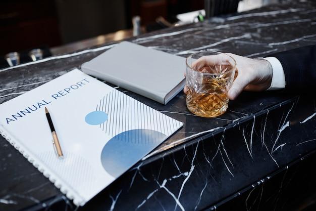 Zamknij się nierozpoznawalny biznesmen cieszący się drinkiem w barze podczas podróży służbowej, miejsce kopiowania