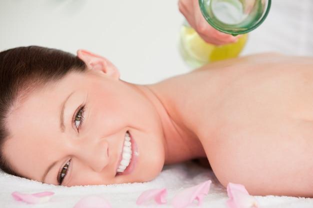 Zamknij się o kobietę o olejku massag zorientowanych na plecach