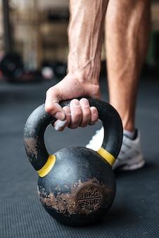 Zamknij się obraz fitness człowieka z kettlebell w siłowni. przygotowuje się do wychowania