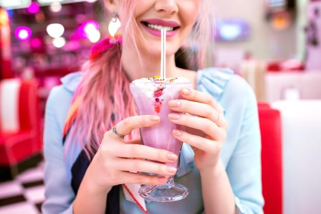 Zamknij się obraz kobiety trzymającej słodkie truskawkowe mleko wstrząsnąć, pin up w stylu retro, pastelowe kolory, vintage amerykańskiej kawiarni