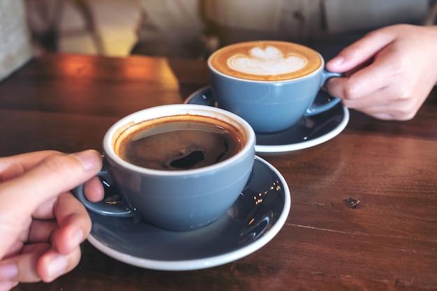 Zamknij się obraz mężczyzny i kobiety brzęczących niebieskich kubków kawy na drewnianym stole w kawiarni