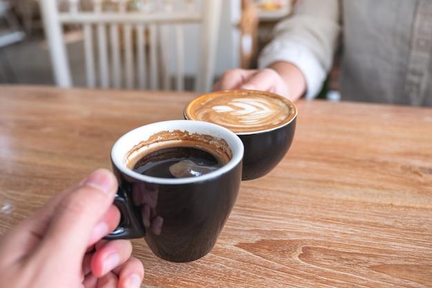 Zamknij się obraz mężczyzny i kobiety, brzęk dwa kubki do kawy na drewnianym stole w kawiarni