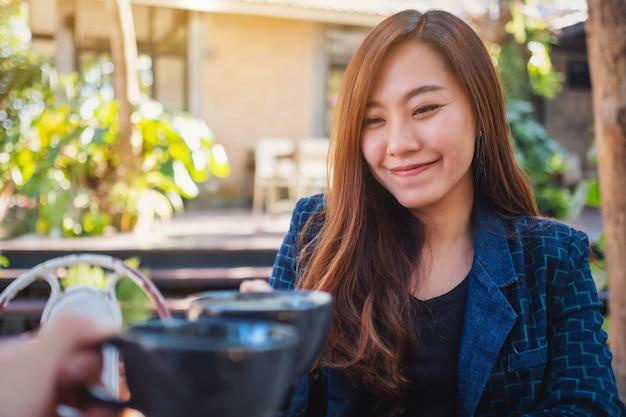 Zamknij się obraz pięknej azjatyckiej kobiety, stukając kubki do kawy z przyjacielem w kawiarni