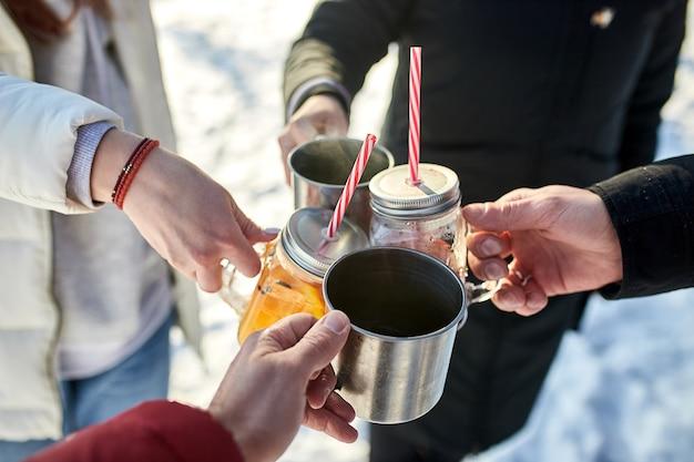 Zamknij się obraz przyjaciół grupy wiwatujących z grzanym winem w zimowym lesie