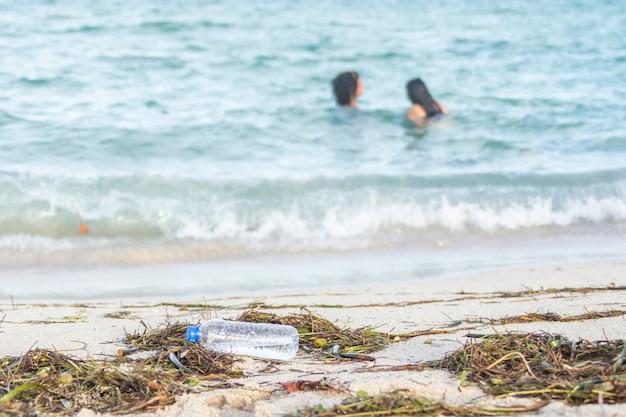 Zamknij się obraz pustej plastikowej butelki z wodą na brudnej plaży wypełnionej wodorostami, śmieciami i odpadami na brudnej, piaszczystej plaży z ludźmi na morzu