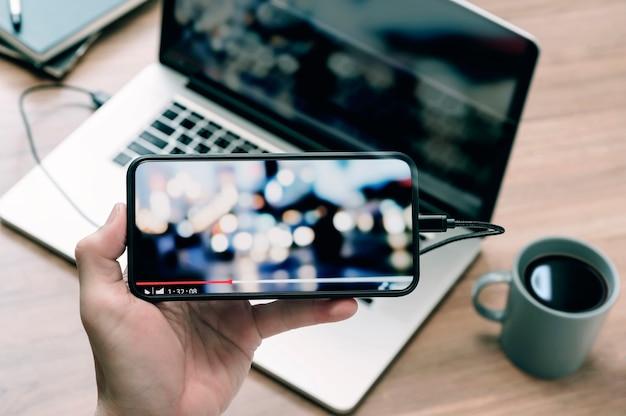 Zamknij się obraz ręki człowieka trzymającego smartfon w widoku poziomym