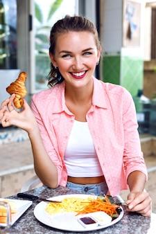 Zamknij się obraz szczęśliwej uśmiechniętej kobiety cieszyć się jej porannym francuskim śniadaniem na tarasie otwartej kawiarni, smaczną żywność ekologiczną. trzymając w ręku francuski rogalik.