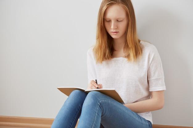 Zamknij się obraz życia całkiem młoda nastolatka siedzi na podłodze i robienia notatek