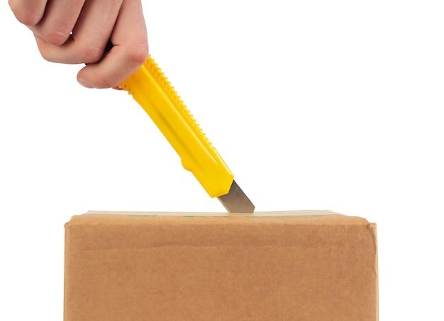 Zamknij się otwarcie kartonu z nożem biurowym.