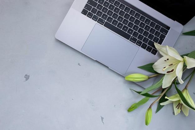 Zamknij się otwarty laptop z kwiatkiem na starym drewnianym biurku. płaski styl świecki