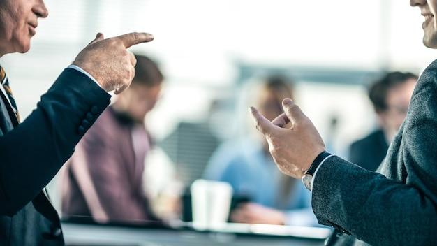 Zamknij się. partnerzy biznesowi kłócą się siedząc przy biurowym stole. zdjęcie z miejscem na kopię