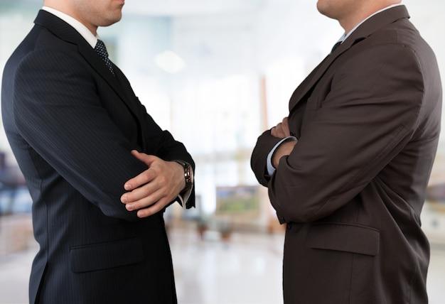 Zamknij się pewni siebie biznesmeni w czarnych eleganckich garniturach ze skrzyżowanymi ramionami