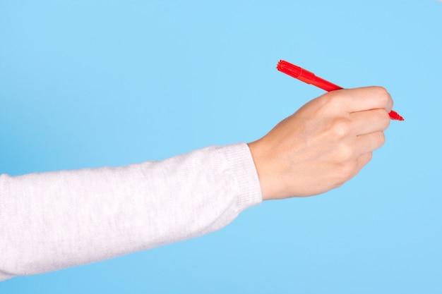 Zamknij się pod ręką z czerwonym pisakiem na białym tle