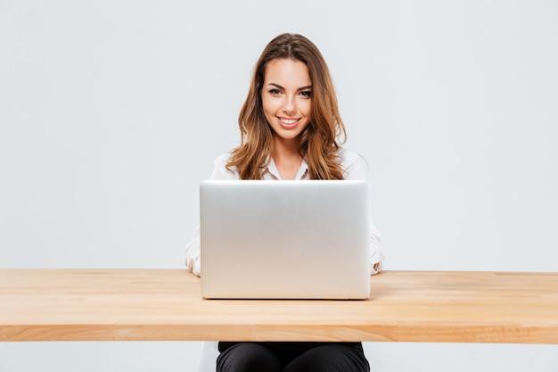 Zamknij się portret atrakcyjnej uśmiechniętej bizneswoman za pomocą laptopa siedząc przy biurku na białym tle