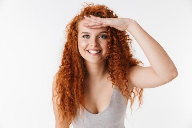Zamknij się portret atrakcyjnej uśmiechniętej młodej kobiety z długimi kręconymi rudymi włosami stojącej na białym tle, patrzącej daleko