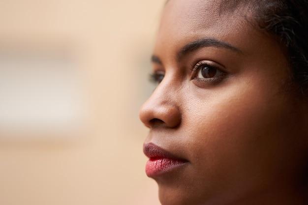 Zamknij się portret atrakcyjnych oczu african american womans patrząc na zewnątrz przez okno