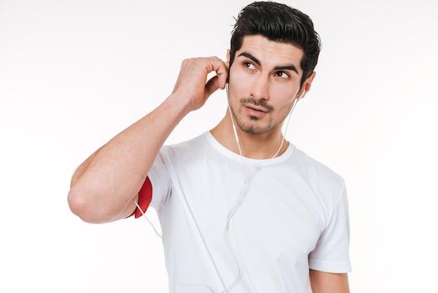 Zamknij się portret młodego sportowca ze słuchawkami, odwracając wzrok na białym tle na białym tle