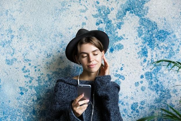 Zamknij się portret młodej kobiety ubranej w sweter i kapelusz na niebieskiej ścianie, słuchając muzyki przez słuchawki, trzymając telefon komórkowy, oczy zamknięte